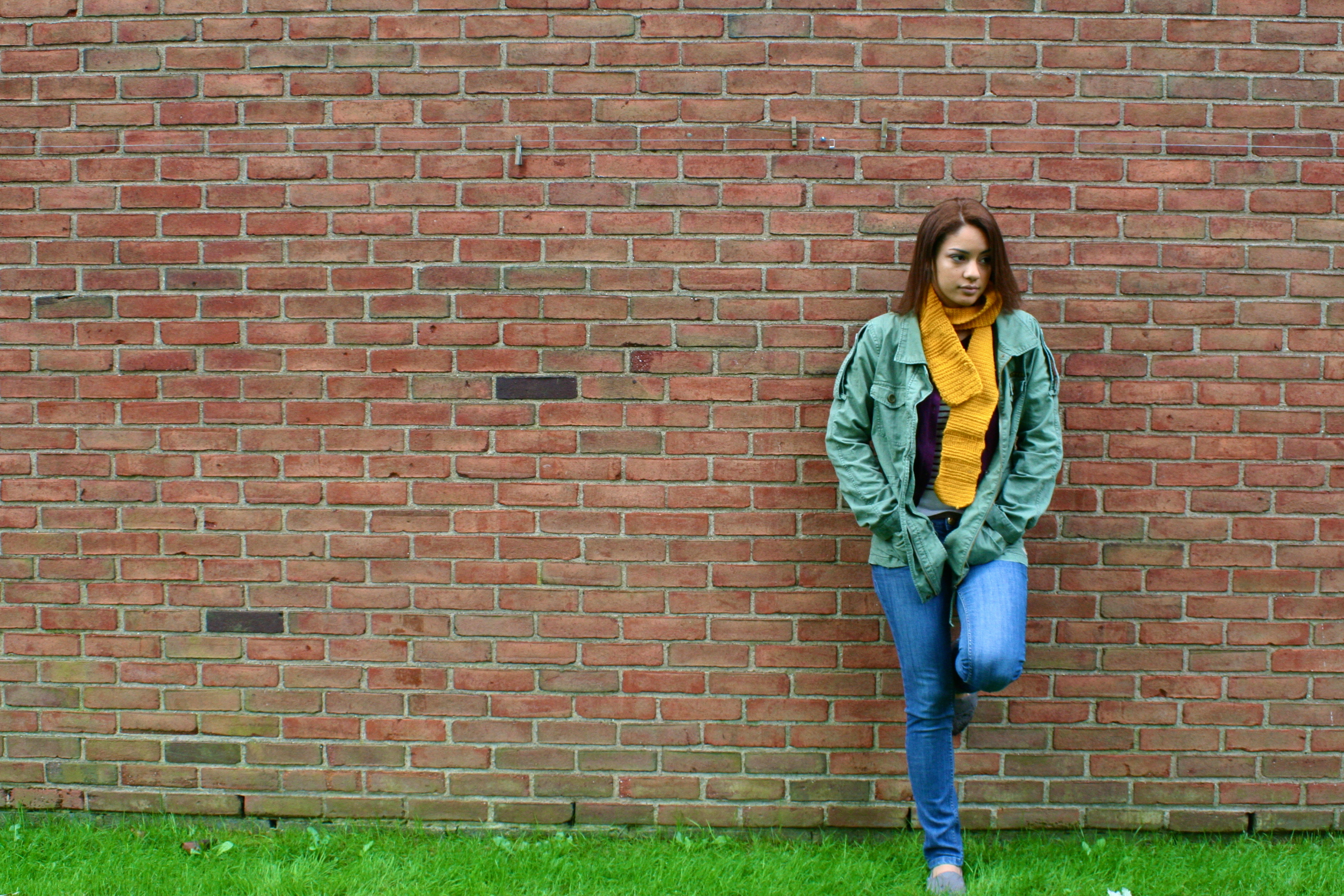 Woman-leaning-on-brick-wall
