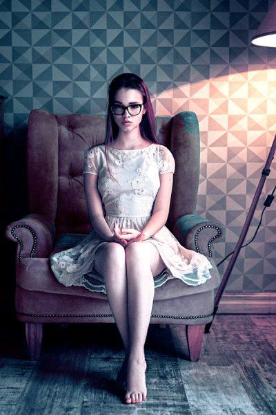薄暗い部屋で椅子に座る女性